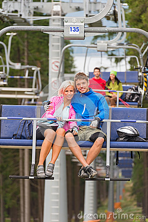 Cuddling young couple sitting on chair lift