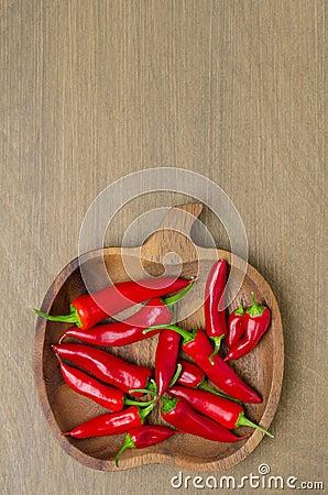 Cuenco de madera con la opinión superior roja de las pimientas de chile (y espacio para el texto)