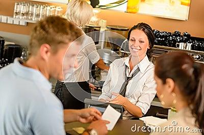 Cuenta que paga de los pares en el escritorio de efectivo del café