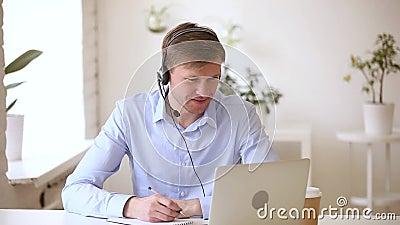 Cuffia avricolare d'uso sorridente dell'uomo d'affari che studia le note di fabbricazione online video d archivio