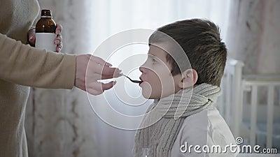 Cuidados infantis, pais despejam xarope para tosse em uma colher para crianças doentes toma remédio para a doença sentada na cama video estoque