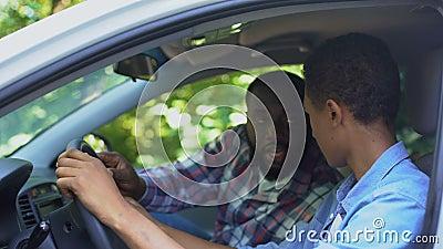 Cuidando dos pais ensinando a dirigir carro, passando tempo juntos, família video estoque
