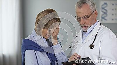 Cuide hablar con su paciente femenino, mujer comienza a llorar, las malas noticias, oncología almacen de metraje de vídeo