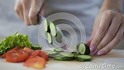 Cuisinier en chef féminin coupant des légumes, faisant cuire la salade fraîche délicieuse pour le déjeuner banque de vidéos
