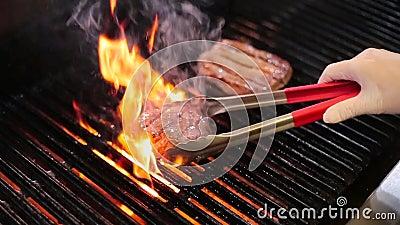 Cuisinier faisant frire la viande sur le gril banque de vidéos
