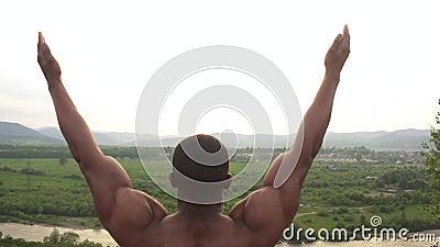 Culturista afroamericano con el cuerpo perfecto que estira en el pico de montaña durante su entrenamiento al aire libre de la mañ almacen de video