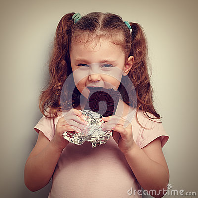 Free Cunning Kid Girl Eating Dark Chocolate With Pleasure And Curious Royalty Free Stock Image - 59519156