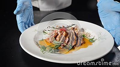 Cuoca al ristorante che presenta piatti pronti con carne a fette di succo, verdure versate con salsa dolce Cucina fine video d archivio