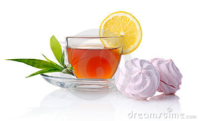 Cup of black tea with lemon, green leaves