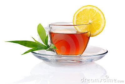 Cup of black tea with lemon and green leaves