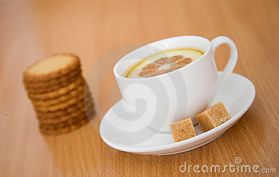 Cup of black tea with lemon, sugar and biscuits