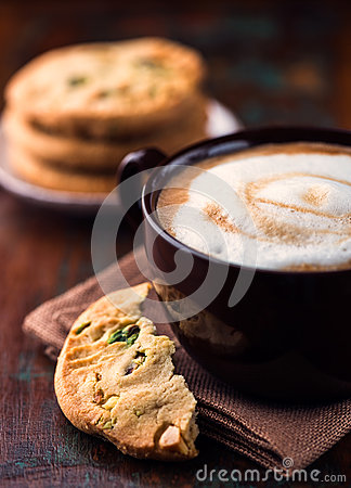 Cup of cafe au lait and pistachio cookie