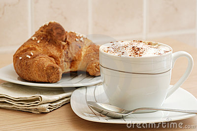 Cup of cappuccino and brioche