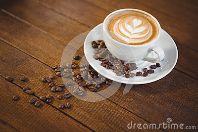 Cup of cappuccino with coffee art and coffee beans Stock Photo