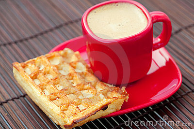 Cup of cappuccino and waffles on a bamboo mat