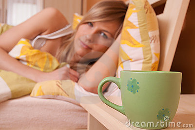 A cup of cofee at bedroom, in background woman