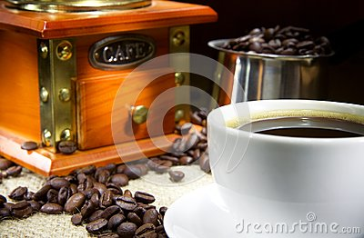 Cup of coffee, beans, pot and grinder on sacking
