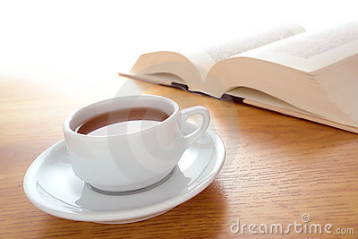 Cup of Coffee and Big Book Leisure on a Wood Table