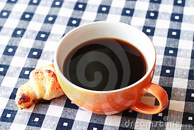 Cup of coffee on blue and white gingham tablecloth