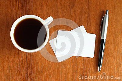 Cup of coffee with business cards and pen