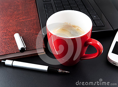Cup of coffee and business objects on the table