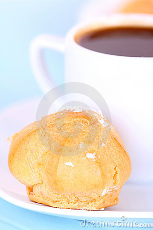 Cup of coffee and cake on blue tablecloth