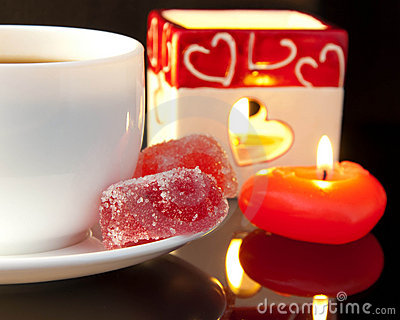 Cup of coffee and candle in the form of heart