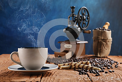 Cup of coffee, coffee grinder, coffee beans in a sack