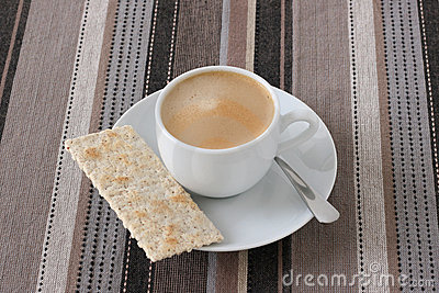 A cup of coffee with cracker
