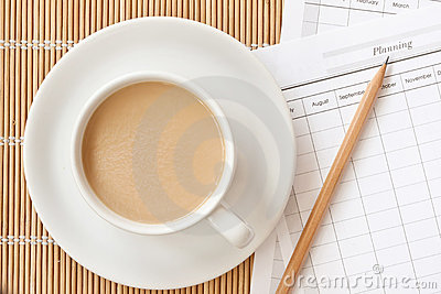 A cup of coffee cup with planning paper