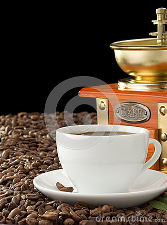 Cup of coffee and grinder on black