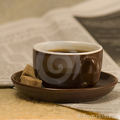 Cup of coffee on newspapers
