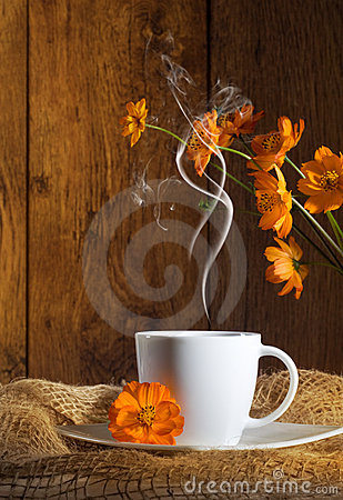 Cup of coffee with orange flowers