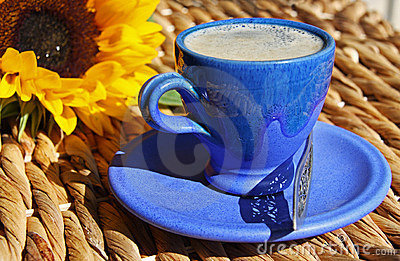 Cup of coffee on a reed table with a sunflower