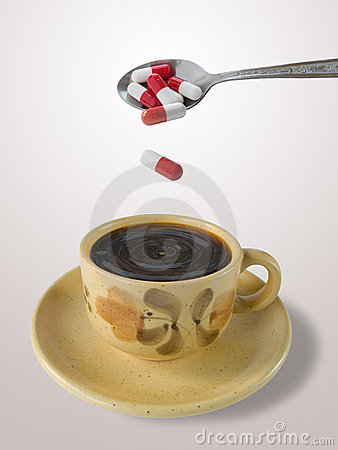 Cup of coffee and spoon with pills
