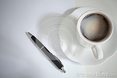 Cup of coffee on table with black pen on breaking