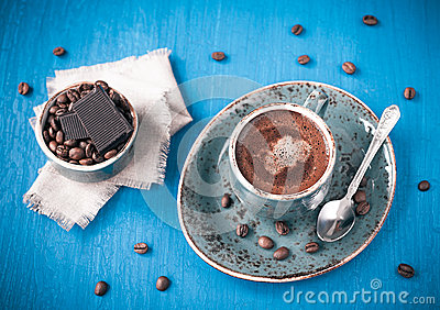 Cup of delicious coffee with chocolate and cream