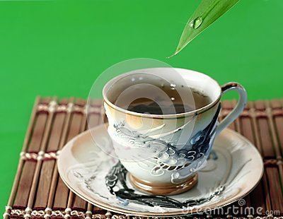 A cup of green tea and a drop of water
