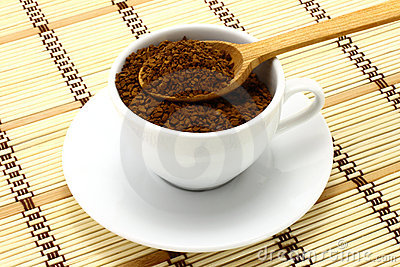 Cup of ground coffee with wooden spoon