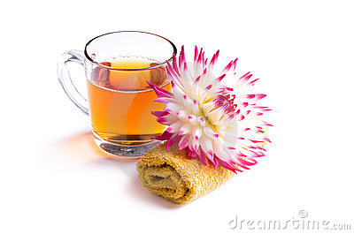 Cup of herbal tea with flower on towel isolated