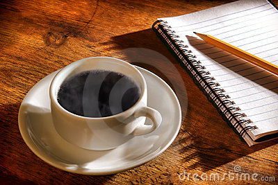 Cup of Hot Black Coffee with Steam and Notebook