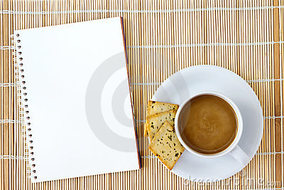 Cup of hot coffee and white sketch book on a mat