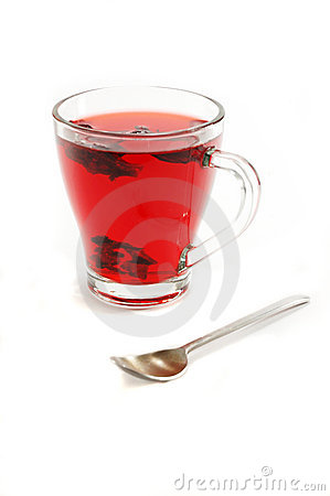 Cup with hot red carcade floral tea and teaspoon