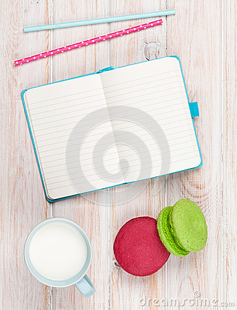 Free Cup Of Milk And Macarons On White Wooden Table With Notepad Stock Photo - 49376990