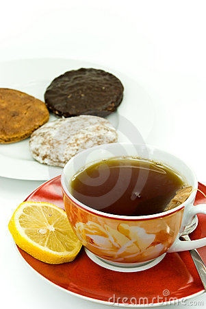 A cup of red tea with mixed cookies