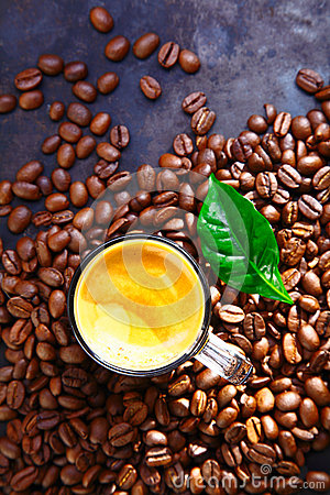 Cup of rich frothy coffee with coffee beans