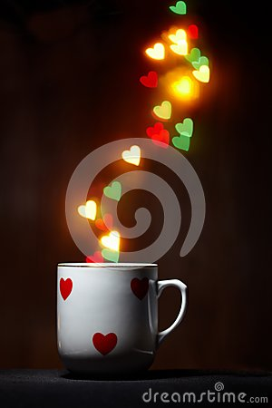 Cup with steam of glowing hearts on dark