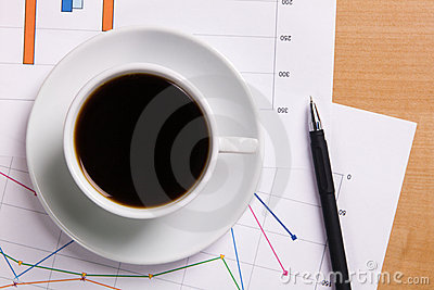 Cup of strong coffee over business diagrams