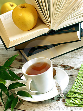 cup of tea, books and apple on wooden