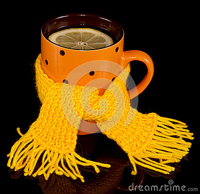 Cup of tea with lemon tied a yellow scarf